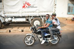 Two men cycle past and point at me. Motorcycles are one of the main forms of transport in Freetown.