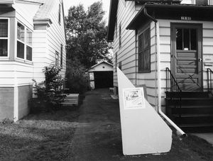 """Garage Interiors"" installation (sidewalk view with poster on drywall 'welcome mat'), Madison, WI, June 1983"