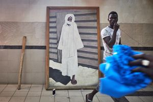 une 13, 2018 - Textile workers pass by a picture of the Saint Cheikh Amadou Bamba Mbacké at the Touba Commercial Center in Dakar. Serigne Touba, as Bamba is also called, watches over numerous street corners, shops and taxis all over Senegal and protects millions of people who wear his picture on amulets.