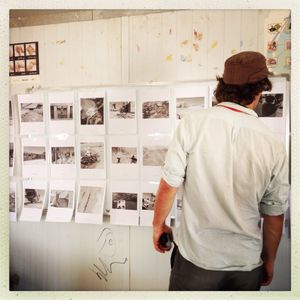 Photographer Michael Christopher Brown looking at the group photo exhibition by teenagers in Za'atari refugee camp