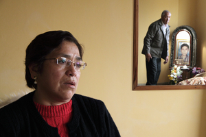 """Reynalda Andagua Gonzales talks about her son, Martín Roca Casas, who disappeared in 1993. Javier Roca, Martín's father, appears in the mirror next to an altar dedicated to the memory of his son. """"He was kidnapped, tortured, murdered and incinerated during the government of Alberto Fujimori"""". Lima, 2009"""