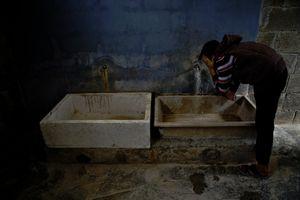 A boy washing his face at the camp's sanitational facilities. © Tom Verbruggen