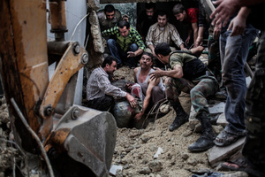 Syrian people are trying to extract from rubble a man wounded by a shelling.