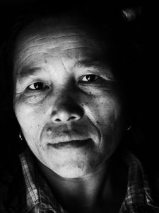 Hmong woman in her very dark and small bamboo house in Laos.