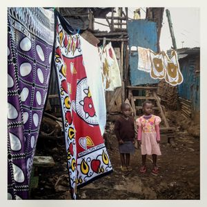 Children stand near clothes hanging on a washing line in Kibera. The Kibera slum is the largest slum in Nairobi with around half a million inhabitants.