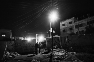 Residents of Tel Rumeida walk home at night.