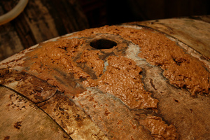 Impurities escape from an open hole in a barrel as apple juice slowly turns into cider