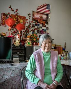 Like many residents, Xian Rong Huang adorns her apartment with brightly colored flowers, family photos, religious icons and other mementos from her life.