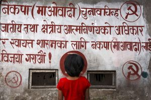 Girl in front of political maoist propaganda. In ten years of war, three hundred children have lost their lives, twenty thousand are orphaned or are destined to face an uncertain future. © Alessio Mamo