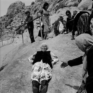 Solomon Mountain. Elderly women are rolling on the polished stone trough. The descent on a back is due to relieve a human from carnal sins lurked in the back. Osh. Kyrgyzstan. 2008.