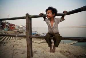 Varanasi, India: The boy is contently watching his herd of water buffalos that are resting on the ghats of the sacred river of Ganges. © Matjaz Krivic