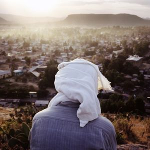 Man meditating on a hill overlooking the city of Aksum.
