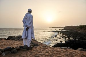 June 17 2018. A follower of the Layene Brotherhood meditates on the cliffs over a holy grotto in Les Almadies in Dakar. He looks out to a point in the sea where allegedly two oceans meet. The Layene say that it is written in the Koran that the Prophet Mohammed would rise again in a place where two oceans come together in order to reform Islam and to restore peace among all Muslims in the world.