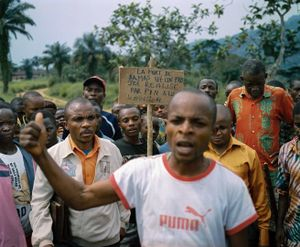 """Angry villagers at Damas' funeral hold up a sign reading, """"The death of Damas is a project realized by PIN in Lulingu on January 17, 2014."""" The murder of Damas implicated an employee of the international nonprofit People in Need, who was accused of enlisting the murderer to commit the act, and RM soldiers who were said to have the murderer  to escape from the town prison. © Diana Zeyneb Alhindawi"""