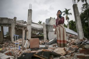 Survivor, Saprina Rajali, 30 years old, grieving as she visit her collapsed house that killed her mother following the earthquake in Pidie Jaya, Aceh province, on December 11, 2016.