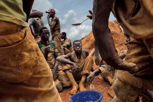 Miners eat lunch from a communal bowl in the mining town of Pluto. They work here to extract rock and sand from a large pit that has taken over a year to excavate. Pluto, Democratic Republic of the Congo, 2013 © Marcus Bleasdale, National Geographic