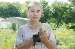 A summery portrait with a tiny black rabbit and a half-eaten apple