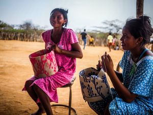 "Wayuu girls sitting in the shadow and knitting a ""mochila"", the traditional bag of the Wayuu people."