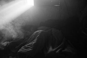 Migrants sleeping with smoke surrounding them.