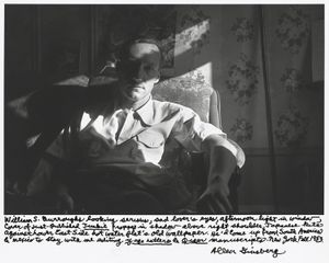 "William S. Burroughs looking serious, sad lovers eyes, afternoon light in window, cover of just published ""Junkie"" propped in shadow above right shoulder, Japanese kite against Lower East Side hot water flats old wallpaper. Hed come up from South America  Mexico to stay with me editing ""Yage Letters""   ""Queer"" maunscripts. New York Fall 1953. © Allen Ginsberg"