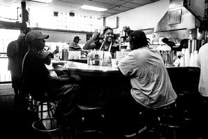 Customer & staff member fist-bump. Moon's Sandwich Shop. Chicago, Illinois. 2013.
