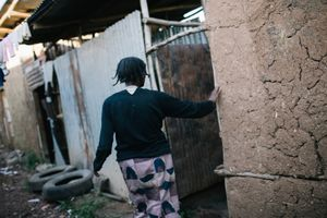 Tesfa feels her way to the compound's shared toilet. Most days this is the only time she spends outside of her small living space.
