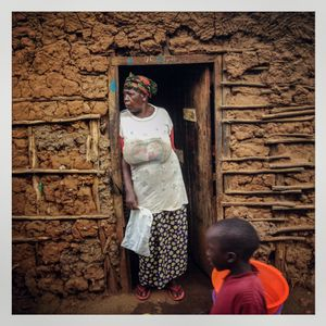 A woman stands in the doorway of her wattle and daub house in Kibera. The Kibera slum is the largest slum in Nairobi with around half a million inhabitants.
