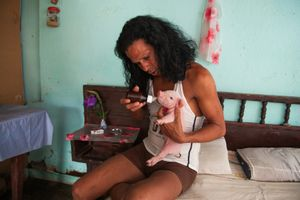 Charito at home with one-week-old piglet, Camaguey © Mariette Allen