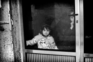 Two Palestinian children watch timidly from the window of their home as their street is turned into a war zone. © Will Hilton
