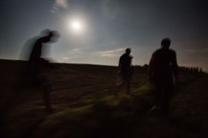 September 2016, Backi Breg, Serbia. Three Algerians walk on Serbian territory towards the Hungarian border through meadows, woods and thickets, up to a couple of meters from the border and from a border patrol which is having a party with a fire, music and beer, but a branch cracks a bit too loud under the foot of one refugee and suddenly four bright lights shine right in on the refugees.