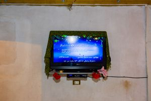 Although the living conditions are extremely poor, any refugee has a TV and a smart-phone. In this photograph, the TV is used to playback the texts of the Koran and to allow the prayer time.