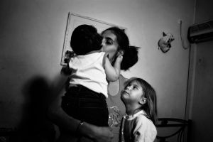 Maria 28 years old with her two children living in a small room given by the government.Athens, Greece Enri Canaj