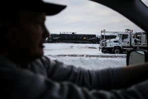 Mike Connelly, a Certified Nursing Assistant (CNA) working in North Dakota in support of the Dakota Access Pipeline, drives past oil tankers being transported by railroad within the Bakken Formation in Glendive, Montana near the North Dakota border in January 2017.