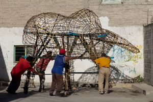 Men moving the structure of a 'torito' (little bull). The structure is the support of layers of paper and paint that will give life to a torito full of firecrackers used to celebrate San Juan de Dios on March 8th.
