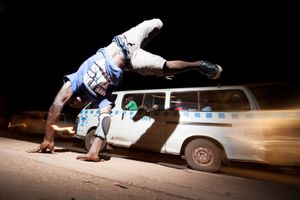 Ismail is dancing in the streets of Kampala, Uganda whilst a Matatu, the local public transport drives by.