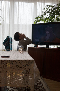 Alex eating sweet chips while watching Tarzan.
