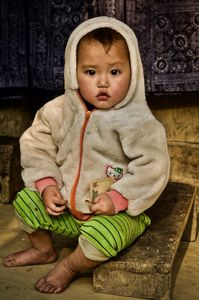 Baby holding money outside a H'mong home in a small village in the Sa pa region.