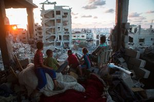 A Palestinian family sits in their destroyed home in a quarter in At-Tuffah district of Gaza city, which was heavily attacked during last Israeli offensive, Gaza city, September 21, 2014.