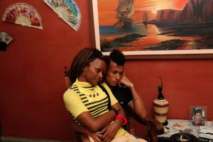 Nomi and Miguel, partners, watching television at Malu's apartment, Havana © Mariette Allen