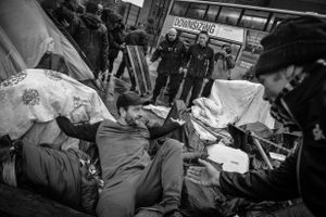 """""""Not in my name"""" a protestor shouts as he lays across the barricade."""