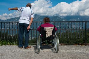 Mrs Angela Invernizzi, 78 years old, with volunteer Mr Renato Luigi Barlassina, looks on the panoramic view of lake Como seen from the top mountain Il Ghisallo, during a day trip on summertime.