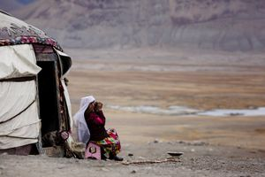 An old kyrgyz woman before her yurt near Chaqmaqtin Lake try to spot her relatives before the night will fall in.