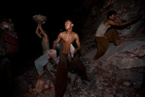 Salt miners load a truck with rock salt after having exploded the mine wall with dynamite at the Khewra salt mine.