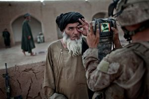 A U.S. Marine from the 3rd Battalion 6th Marines, records the biometric data of a villager at a mosque. © Adam Ferguson