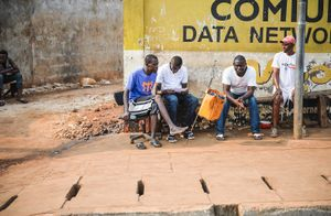 Men sit and converse at the side of the road.