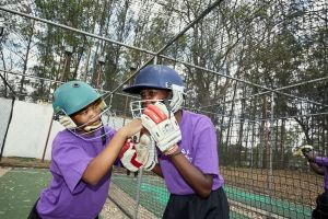 Vice captain Mary helps one of her teammates close her helmet during batting practice, Blantyre, Malawi, 2016.