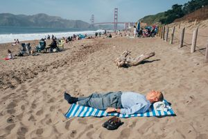 An old gentleman taking a nap on China Beach. San Francisco, California.