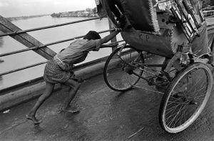 © 2014, Stephen Shames — Bangladesh. Boy pushes rickshaw up incline.
