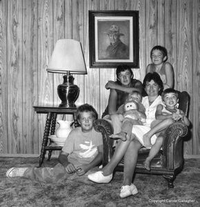 Downwinder Diane Nielson and her children, sitting beneath their prized painting of John Wayne. Henderson, Nevada, 1986