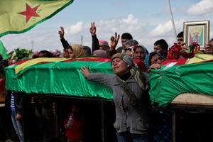 At a cemetery in Kobane, Syria, on 2 April, 2015, mourners stand by the coffine of thier loved ones who was  killed during clashes with the Islamic State in one of the frontlines of Kobane, Syria.